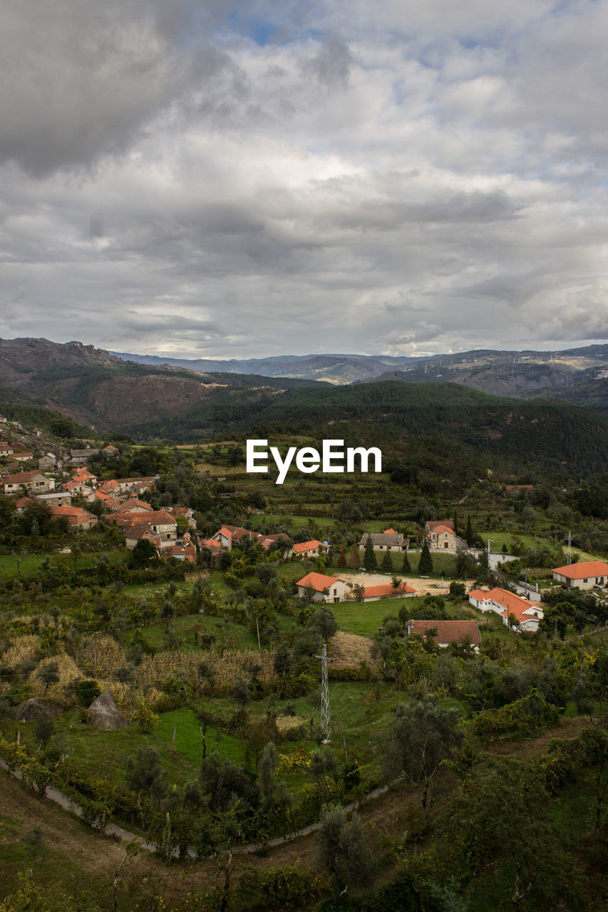 High Angle View Of Village And Mountains Against Cloudy Sky