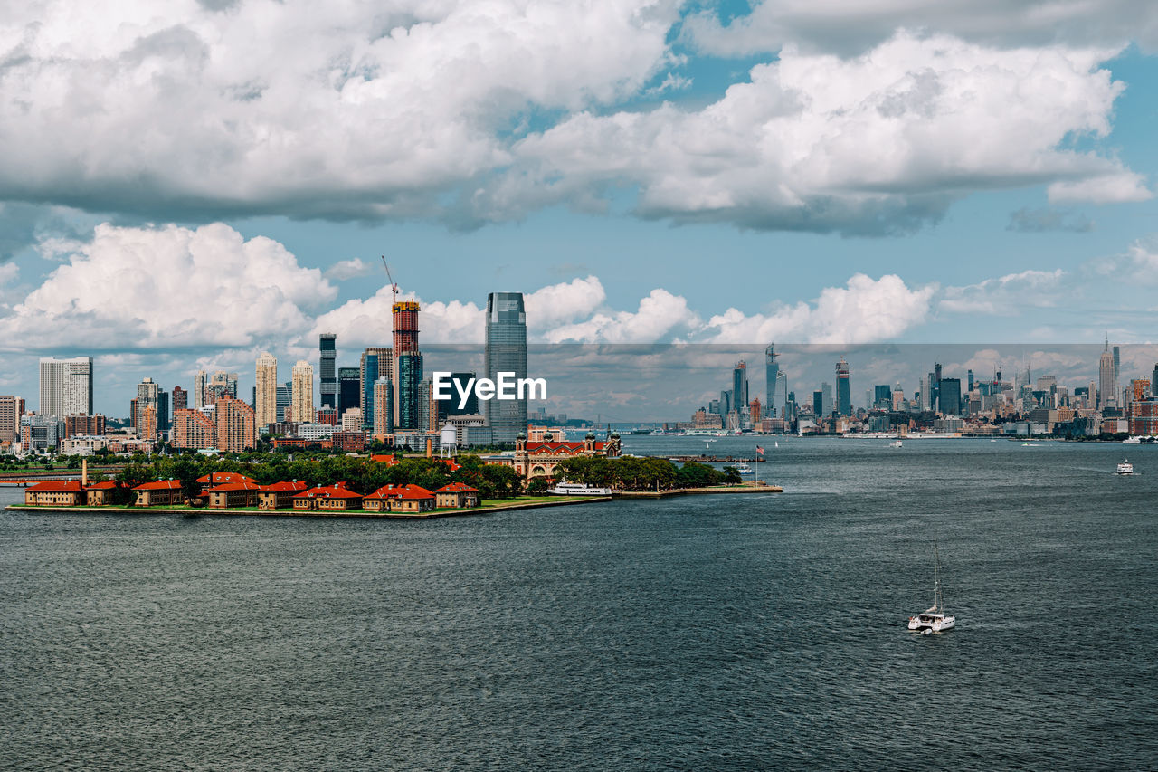 built structure, building exterior, architecture, cloud - sky, water, city, sky, building, nautical vessel, sea, waterfront, transportation, nature, office building exterior, skyscraper, day, no people, urban skyline, cityscape, outdoors, tall - high, modern, financial district, passenger craft