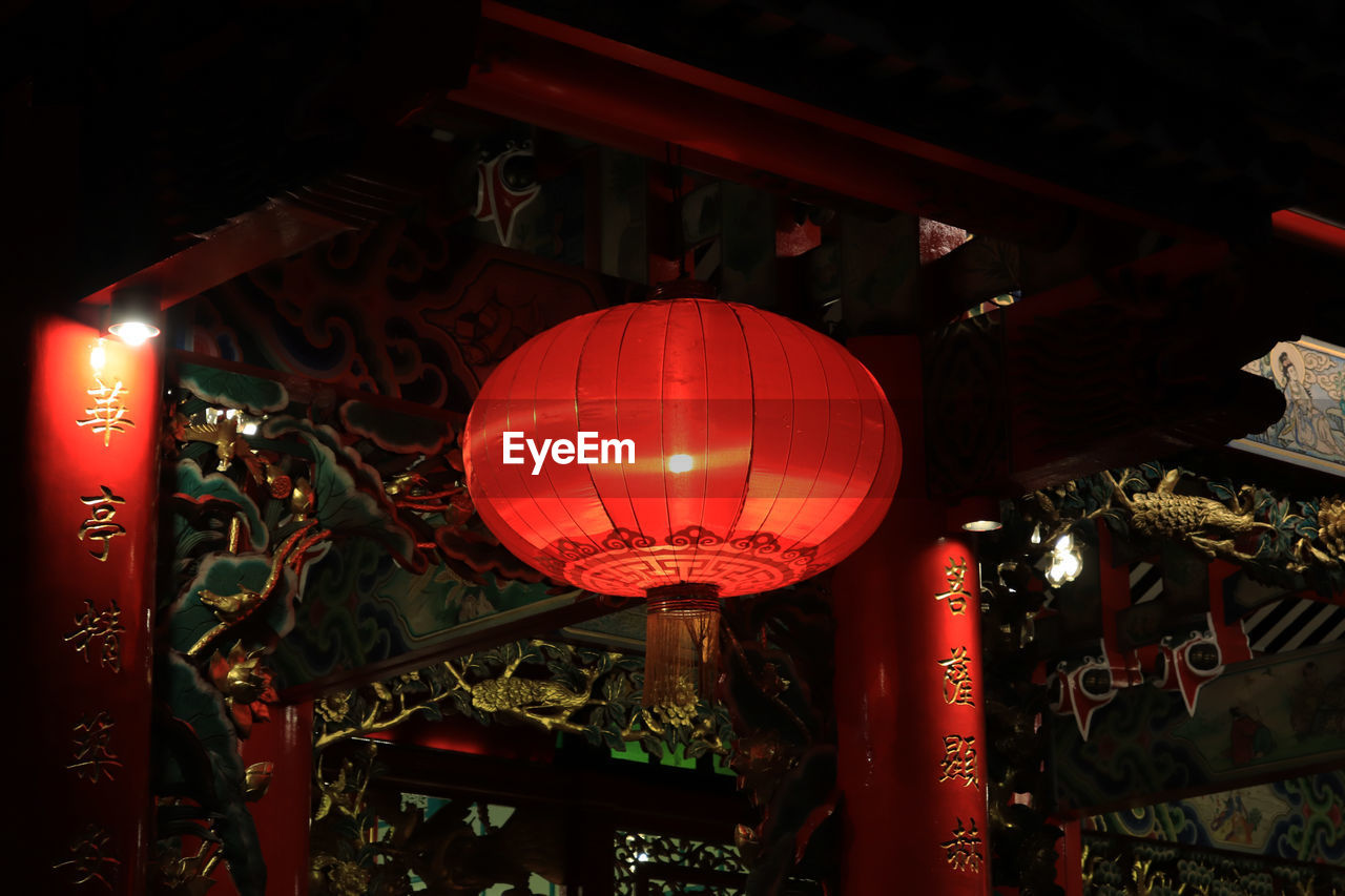 lighting equipment, lantern, red, illuminated, chinese lantern, decoration, hanging, text, no people, script, communication, low angle view, non-western script, built structure, religion, belief, architecture, paper lantern, chinese new year, festival
