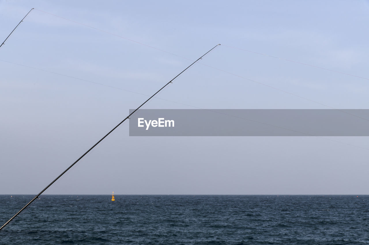 sea, horizon over water, sky, water, horizon, tranquility, sailboat, nature, waterfront, tranquil scene, no people, beauty in nature, nautical vessel, scenics - nature, day, outdoors, transportation, non-urban scene, fishing rod