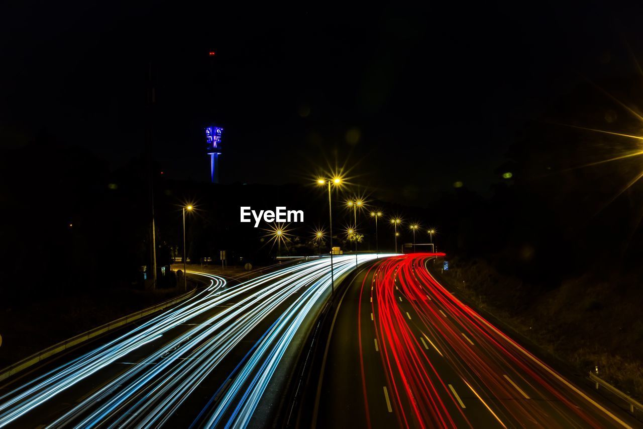 illuminated, night, light trail, long exposure, motion, transportation, lighting equipment, street, speed, city, street light, architecture, blurred motion, road, no people, direction, tail light, the way forward, glowing, light - natural phenomenon, outdoors, multiple lane highway, vehicle light