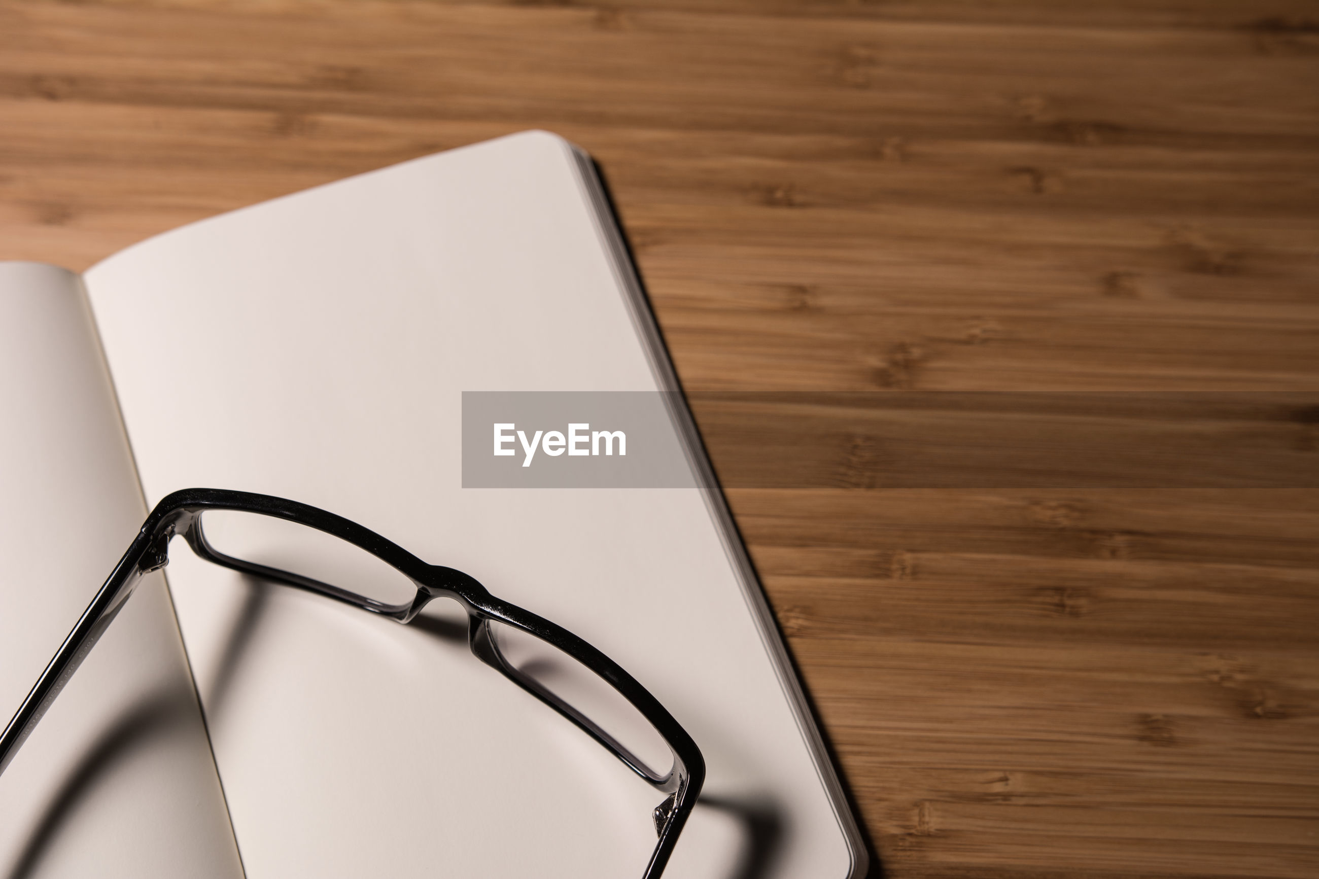 Close-up of open book with eyeglasses on wooden table