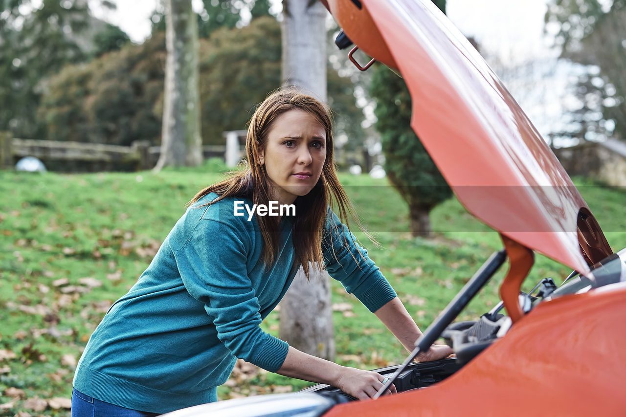Sad or angry beautiful woman inspecting the engine for car