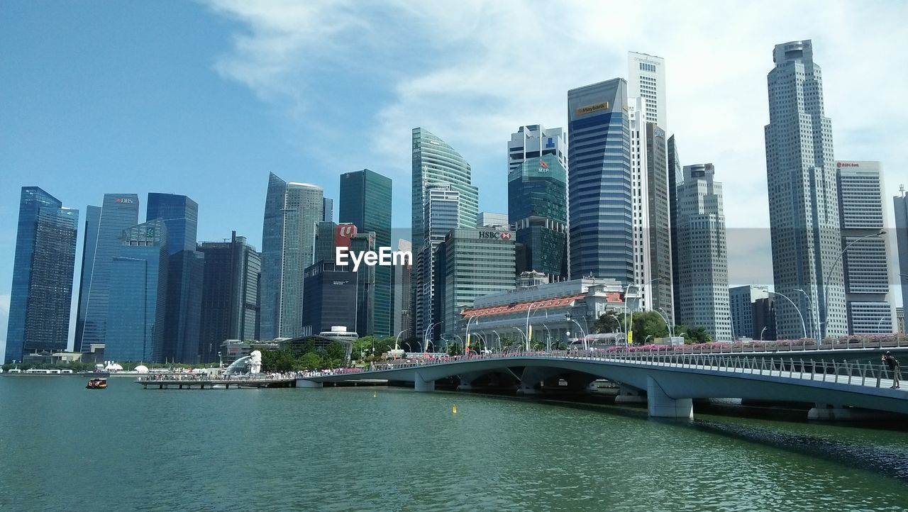 View Of City By River And Buildings Against Sky