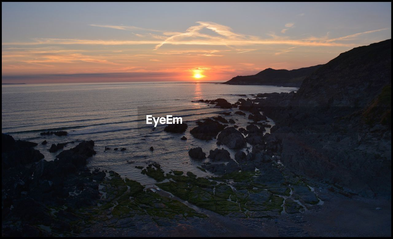 sky, sunset, water, scenics - nature, beauty in nature, sea, tranquility, tranquil scene, beach, land, cloud - sky, nature, horizon over water, rock, horizon, sun, idyllic, orange color, rock - object, no people, outdoors, rocky coastline