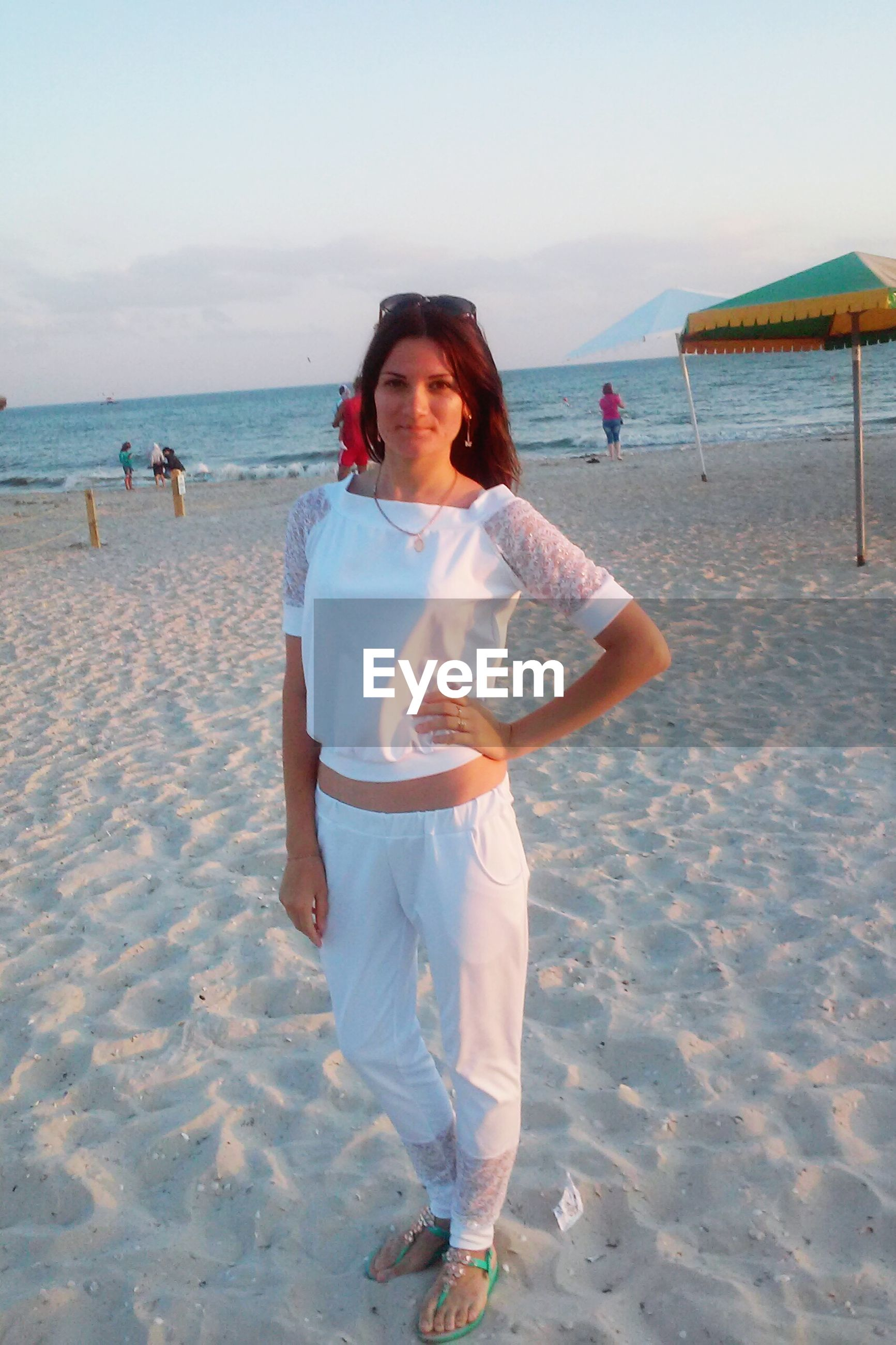 beach, sand, sea, shore, water, lifestyles, leisure activity, horizon over water, sky, vacations, person, casual clothing, full length, childhood, incidental people, looking at camera, front view, nature