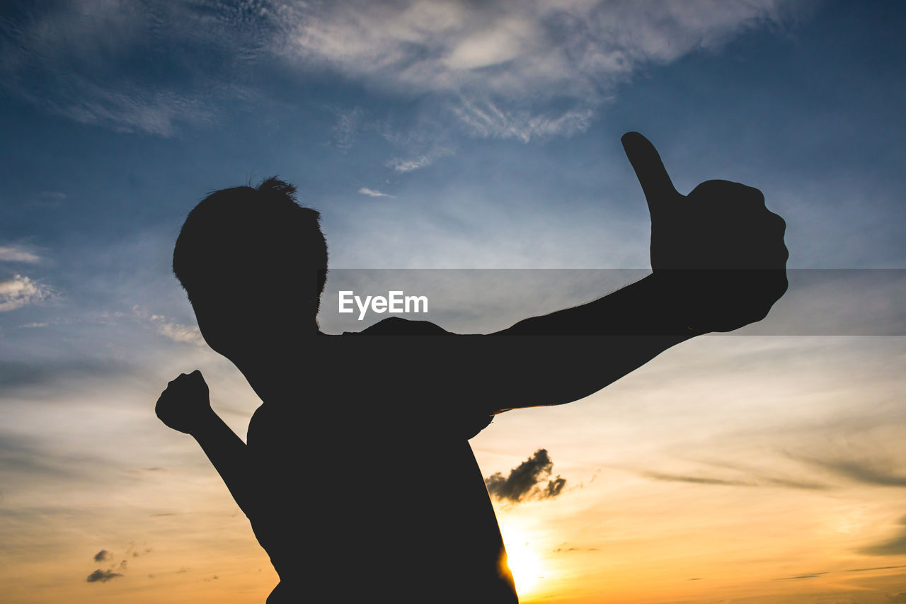 Silhouette man gesturing thumbs up against sky during sunset
