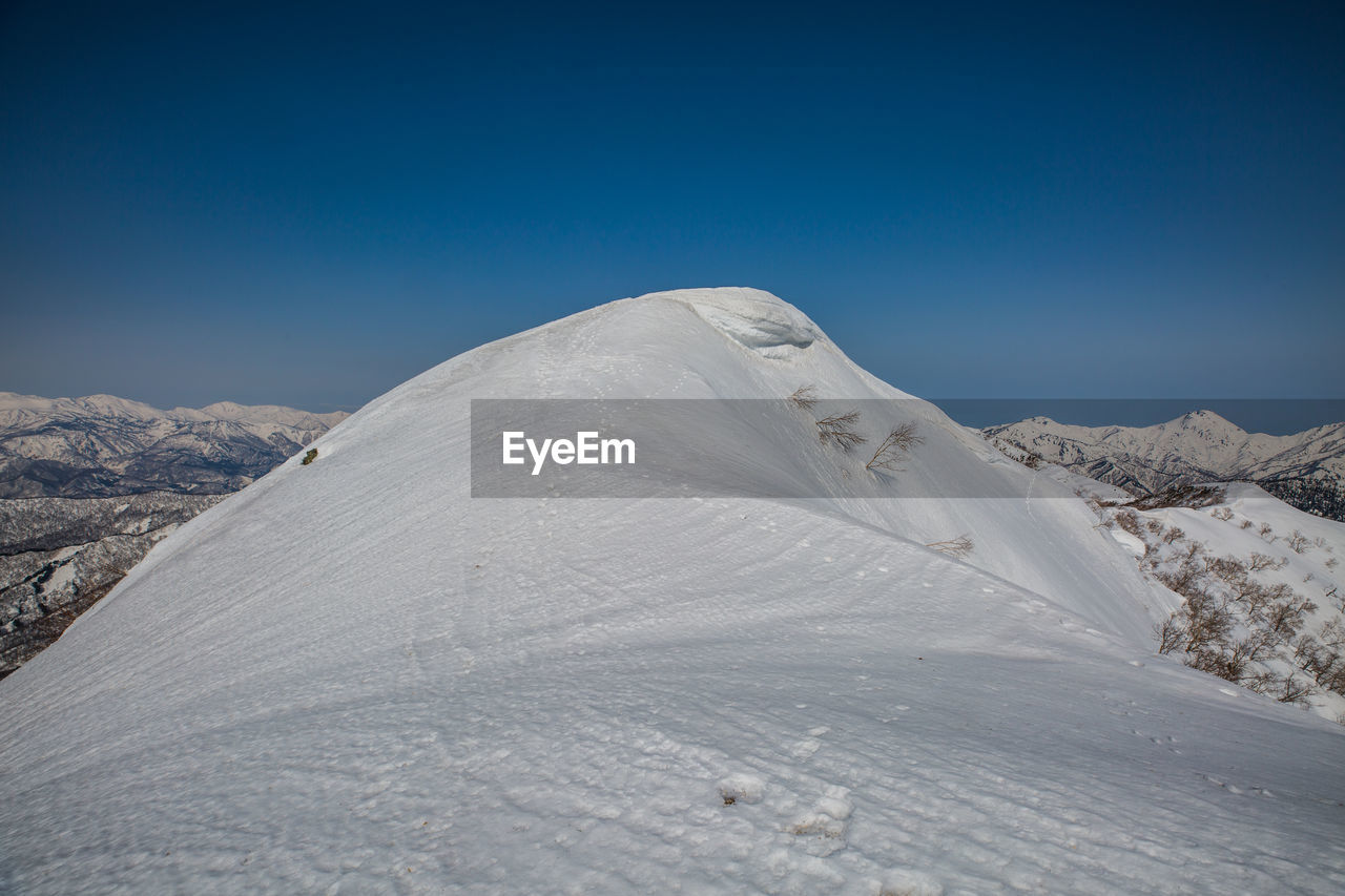 sky, scenics - nature, beauty in nature, mountain, tranquil scene, tranquility, snow, blue, winter, non-urban scene, environment, landscape, cold temperature, clear sky, nature, no people, day, idyllic, snowcapped mountain, mountain range, outdoors, climate, arid climate, mountain peak