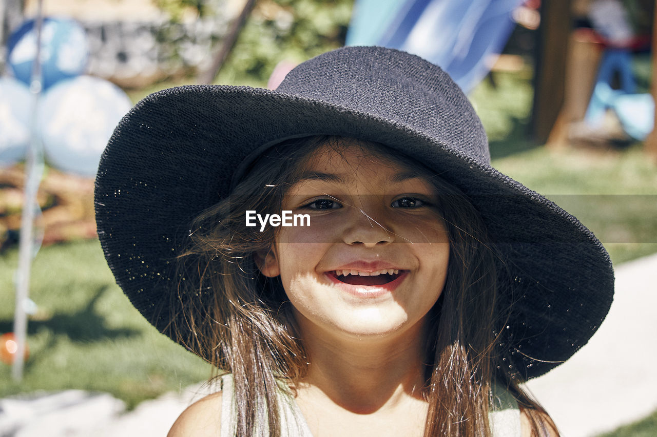 Close-Up Portrait Of Cheerful Girl Wearing Hat At Playground