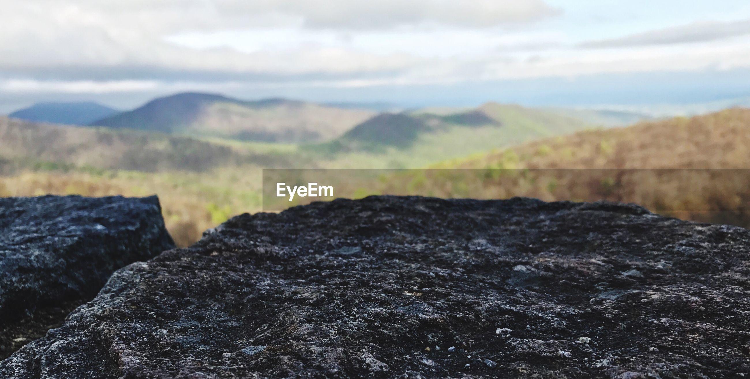 CLOSE-UP OF ROCKS ON LANDSCAPE AGAINST SKY