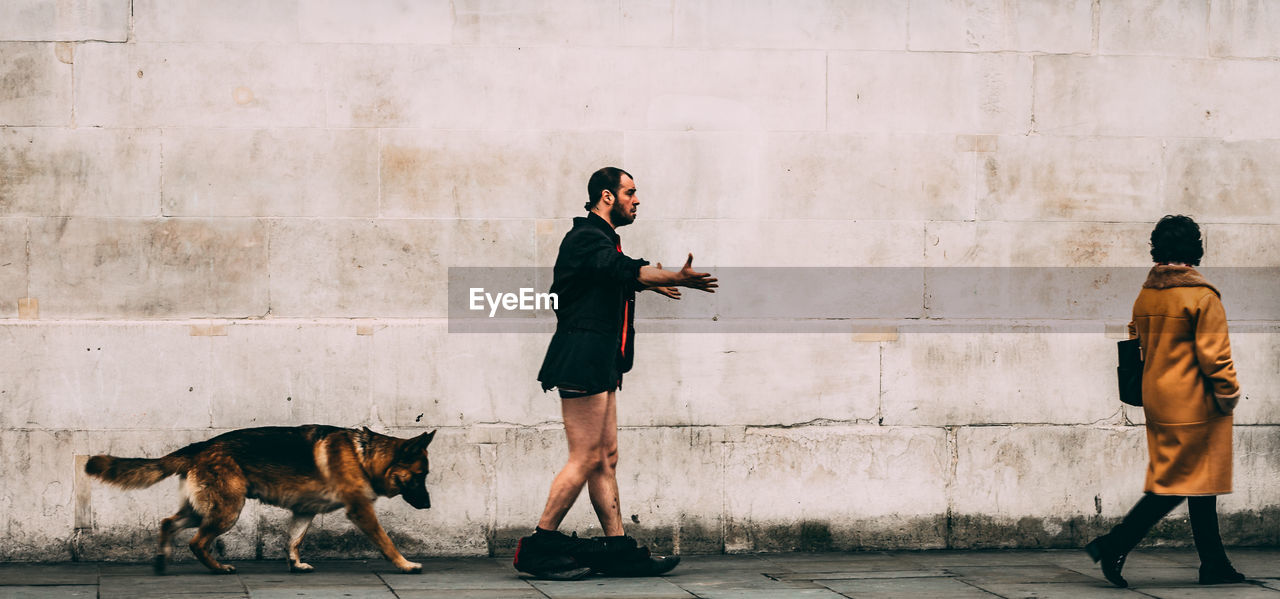 Side View Of Man With Pants Down Walking By Dog And Woman Against Wall
