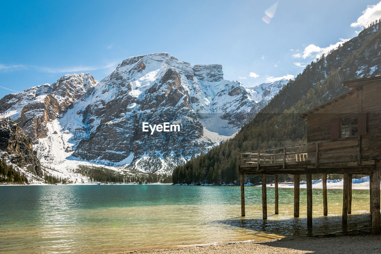 mountain, water, beauty in nature, scenics - nature, sky, cold temperature, winter, snow, nature, tranquil scene, mountain range, tranquility, waterfront, built structure, architecture, no people, idyllic, snowcapped mountain, outdoors, mountain peak