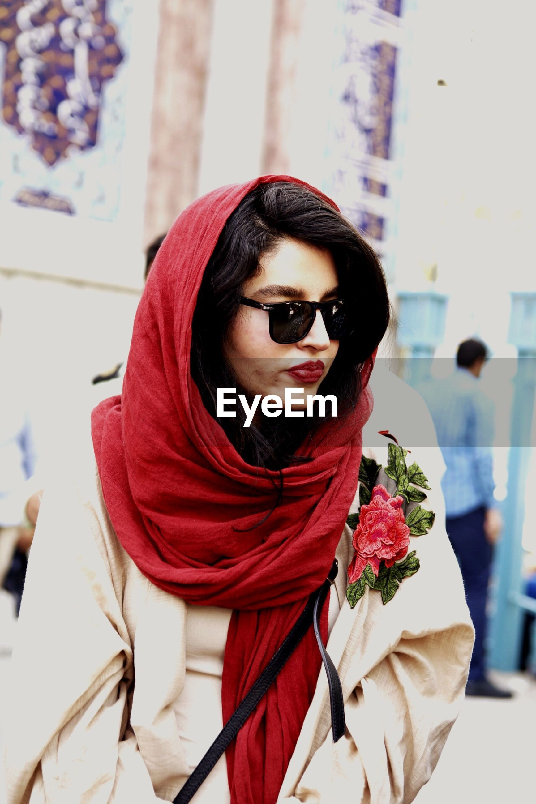 Beautiful woman wearing red scarf in city