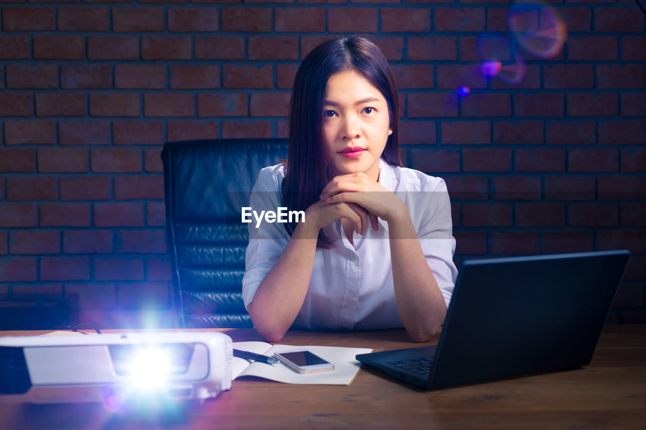 Portrait Of Businesswoman With Illuminated Projector Sitting In Office