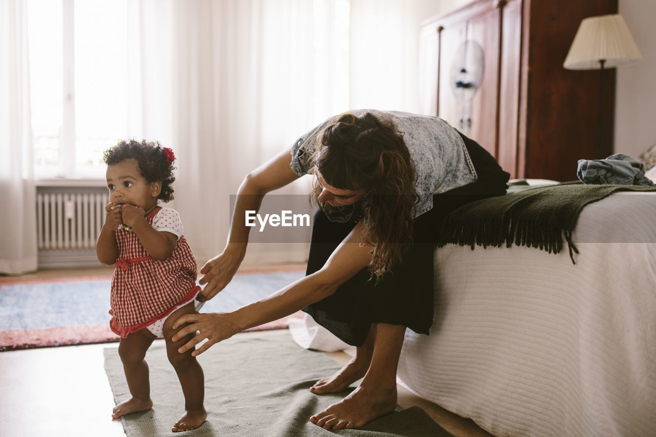 Mid adult woman adjusting diaper of daughter while sitting on bed at home
