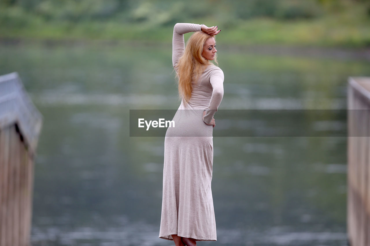 SIDE VIEW OF WOMAN STANDING AT WATER