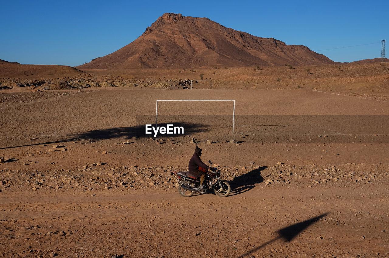 MAN WITH UMBRELLA ON DESERT