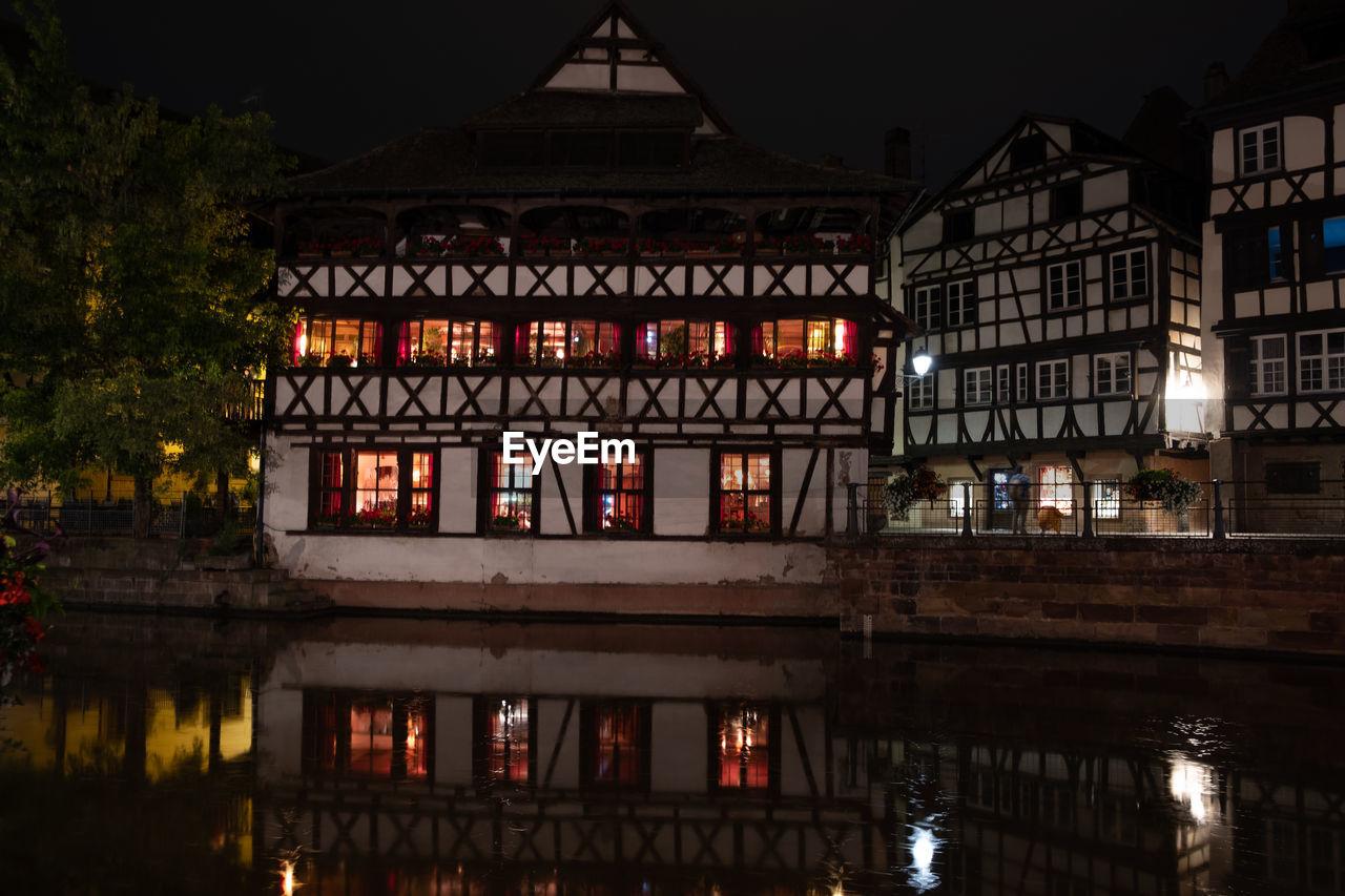REFLECTION OF ILLUMINATED BUILDING IN LAKE