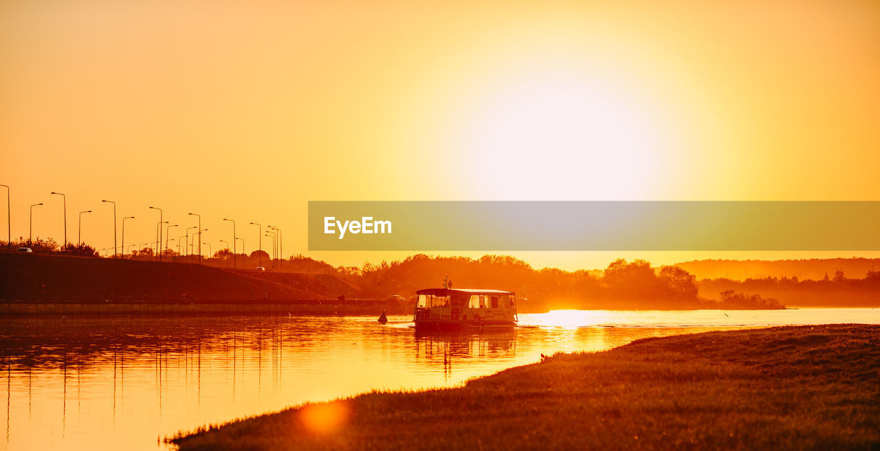 sunset, water, sun, orange color, transportation, nautical vessel, river, mode of transport, sunlight, reflection, waterfront, nature, beauty in nature, sky, silhouette, outdoors, scenics, no people, tranquility, sailing, clear sky, architecture, day