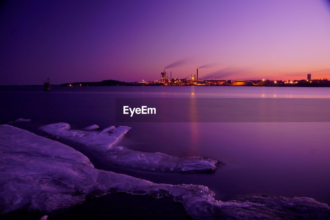 water, sky, sea, sunset, nature, waterfront, rock, reflection, tranquility, rock - object, no people, illuminated, scenics - nature, solid, purple, tranquil scene, architecture, dusk, outdoors, construction equipment