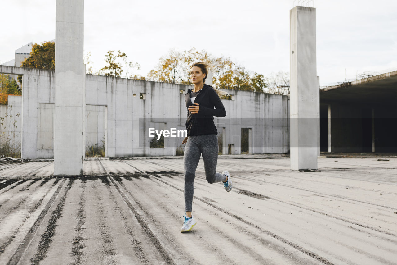 Full Length Of Young Woman Running On Footpath