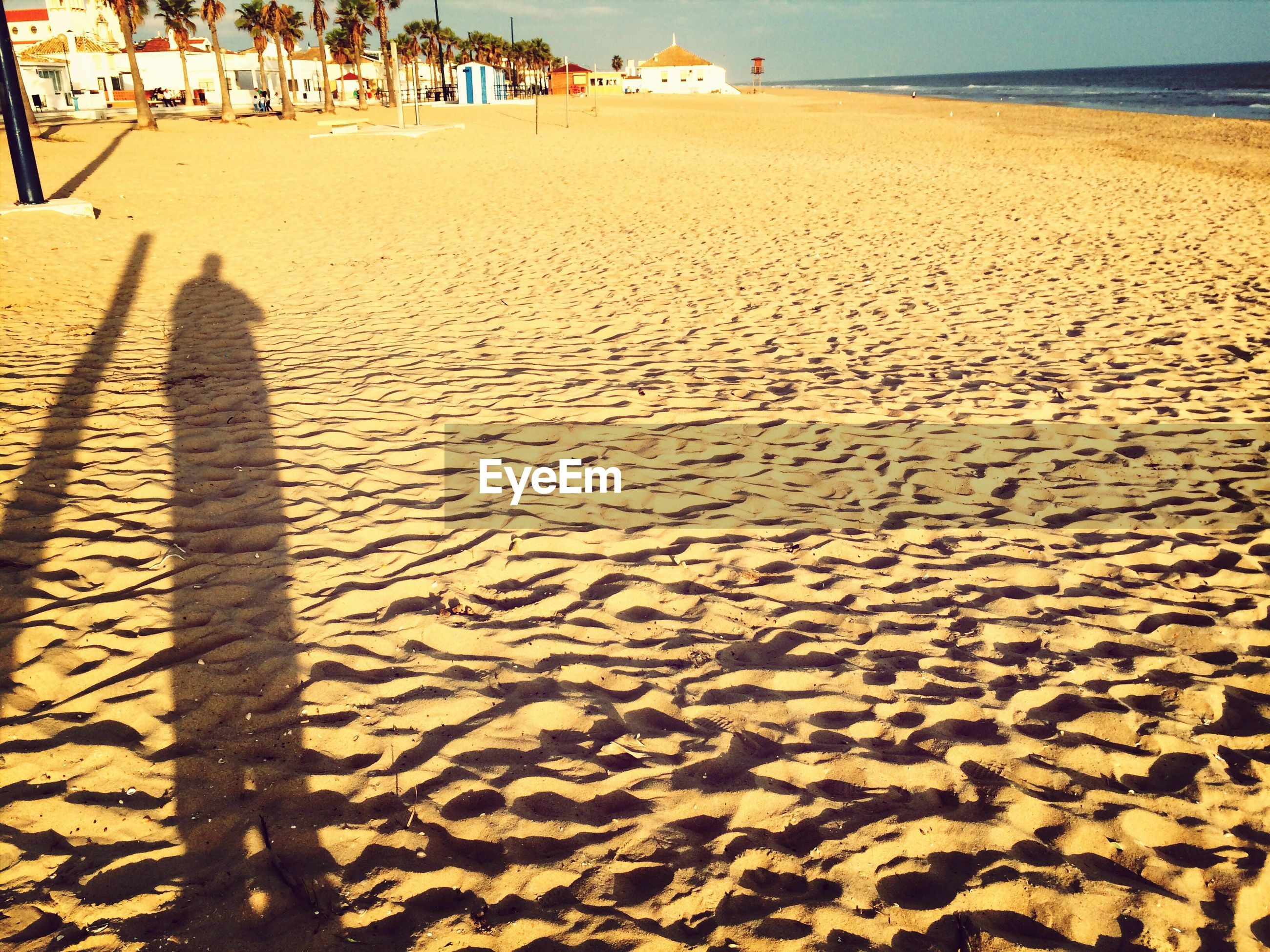 Shadow of person on sandy at beach