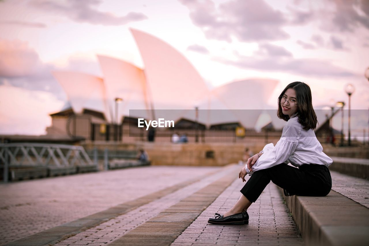 Side view portrait of woman sitting on steps against sydney opera house