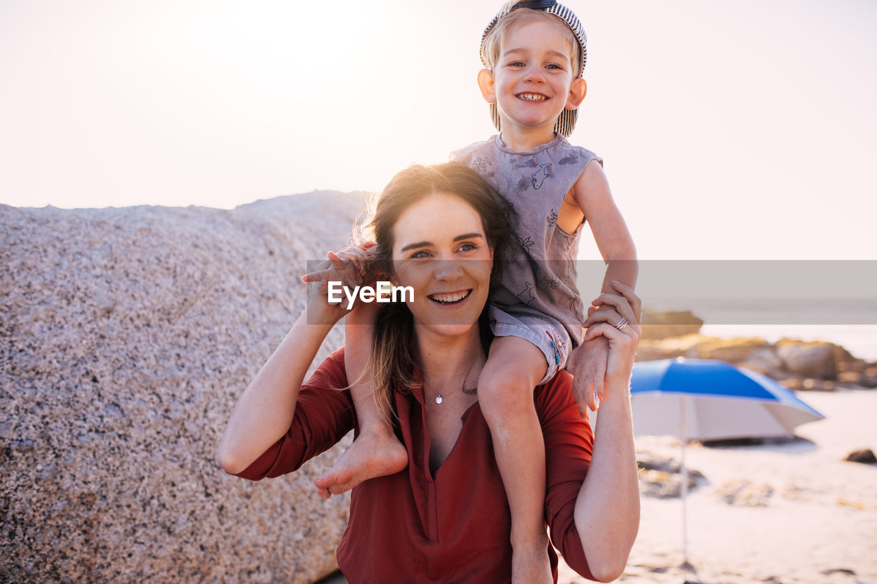 happiness, smiling, looking at camera, portrait, emotion, land, beach, women, leisure activity, bonding, two people, togetherness, sunlight, child, nature, childhood, front view, teeth, females, positive emotion