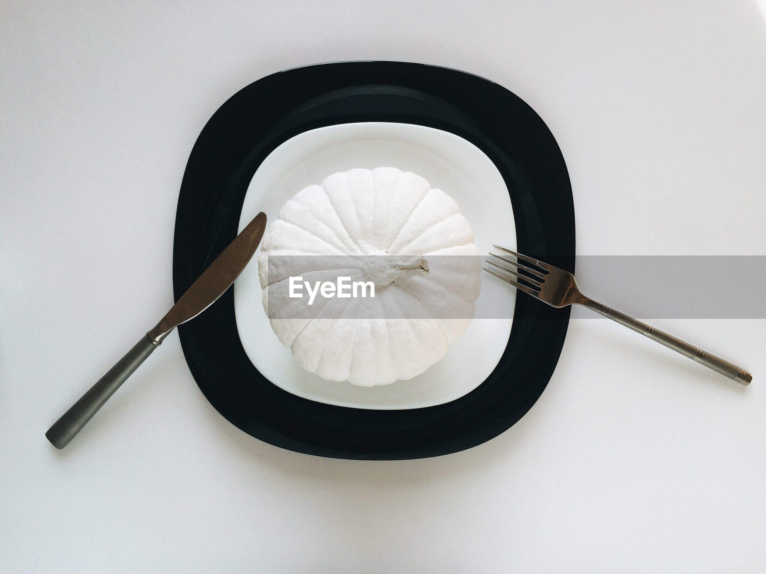 Directly above shot of white pumpkin in plate at dining table