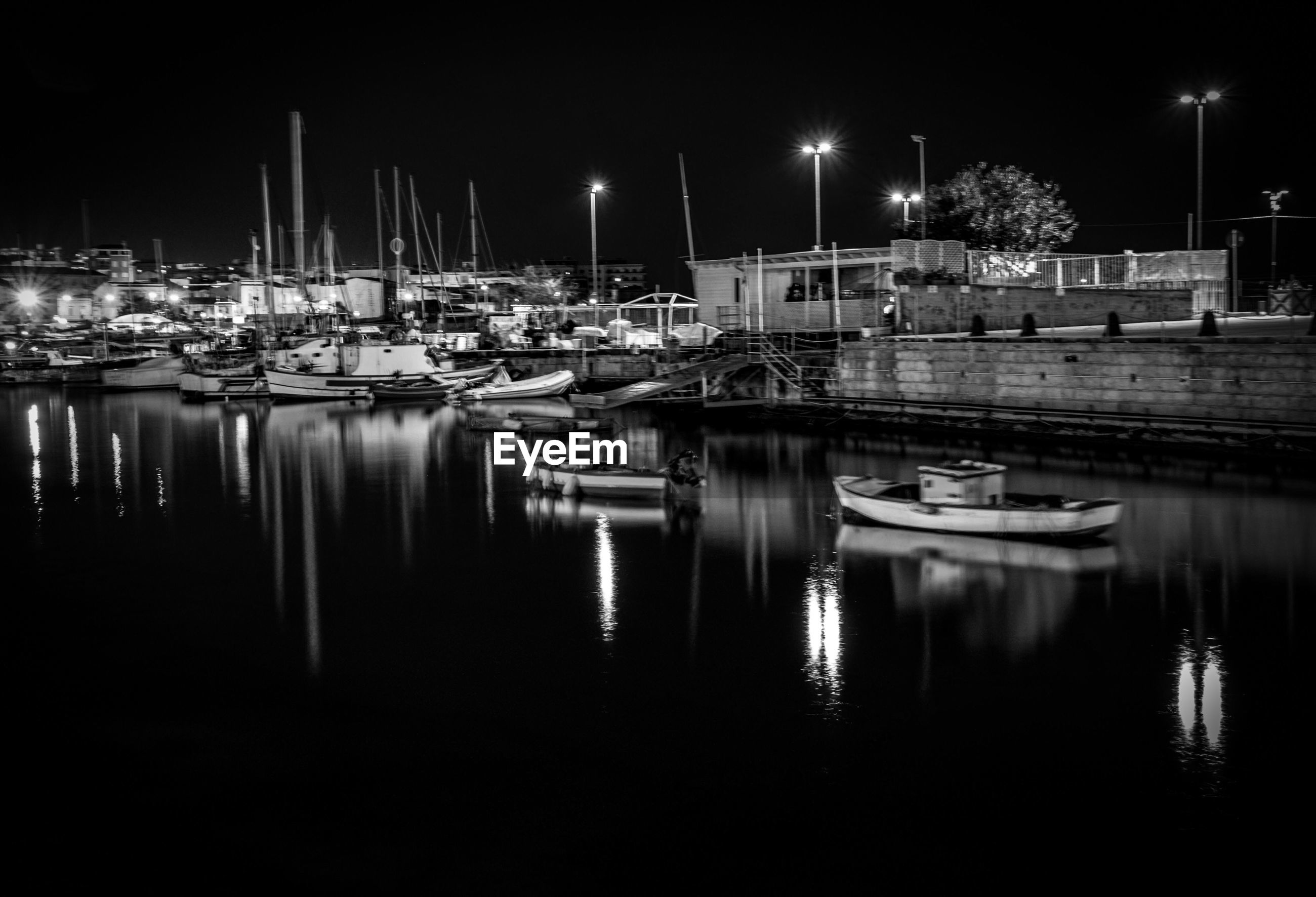 BOATS MOORED AT HARBOR AT NIGHT