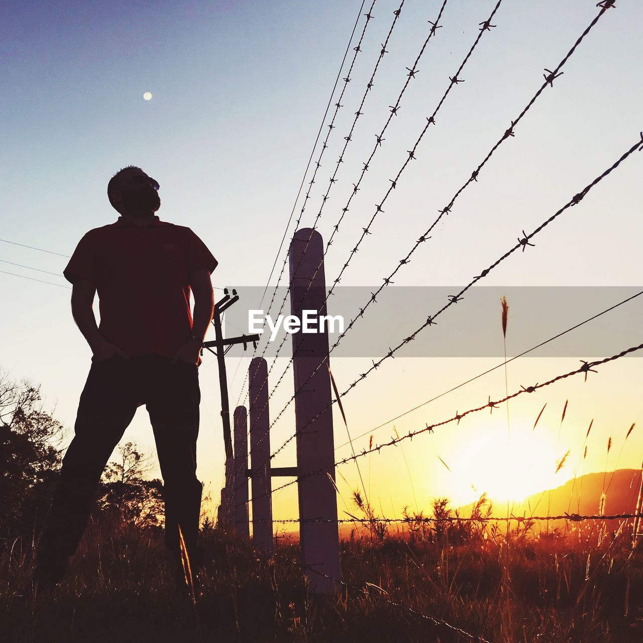 Man Standing On Field By Barbed Wire Against Sky During Sunset