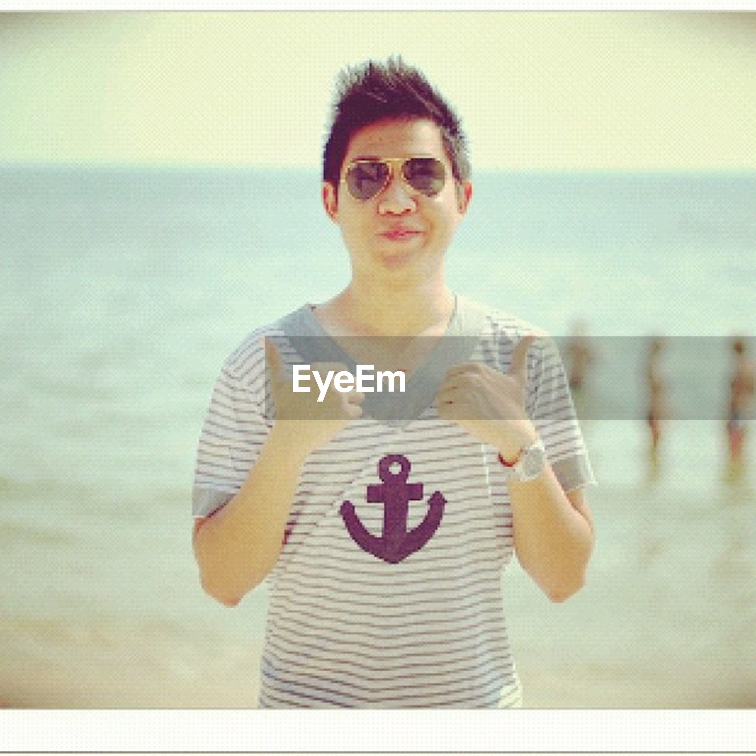 portrait, sea, looking at camera, person, water, front view, young adult, lifestyles, leisure activity, focus on foreground, beach, horizon over water, smiling, sunglasses, happiness, casual clothing, waist up, standing