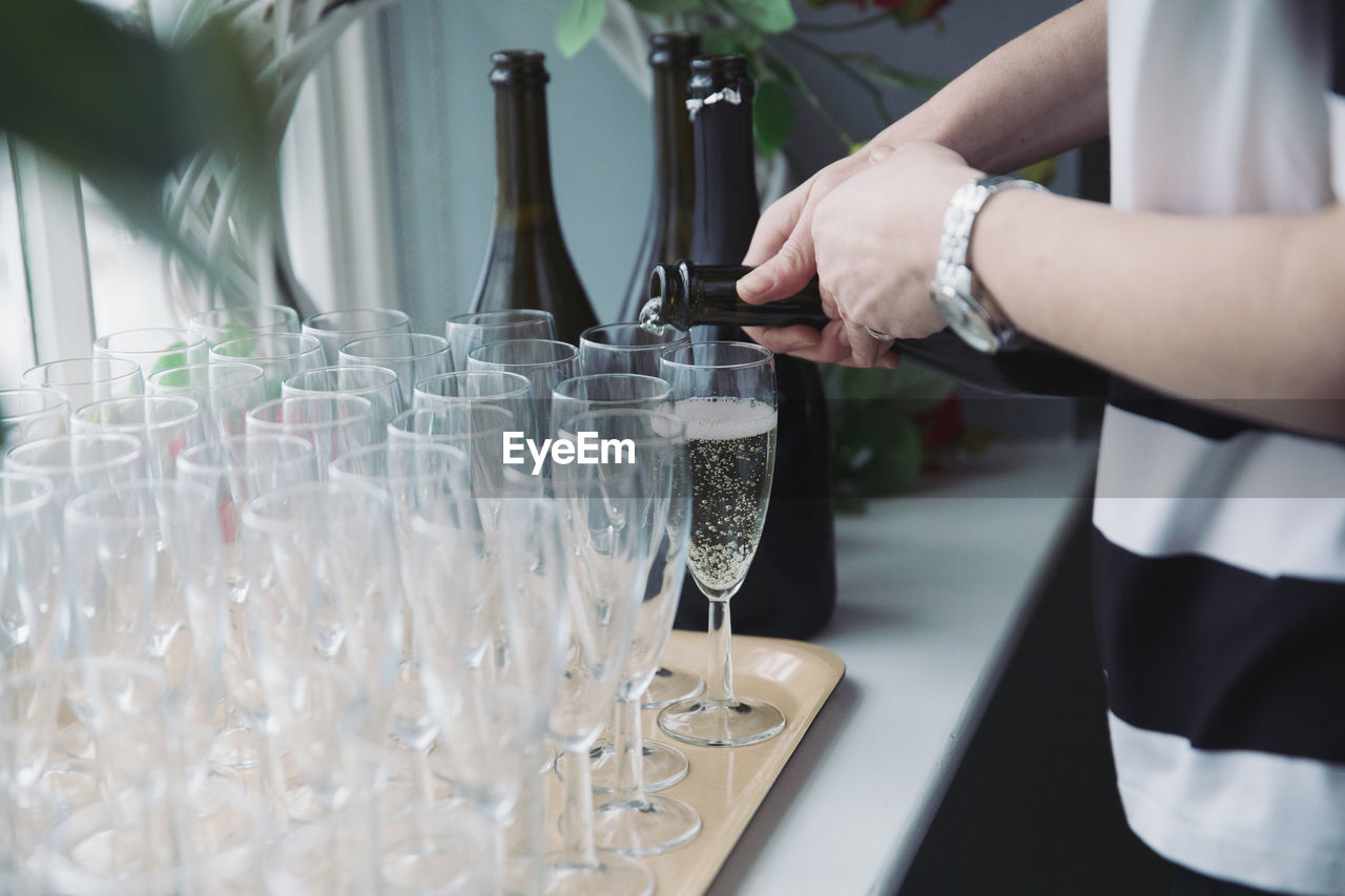 Close-up of woman pouring glass on table
