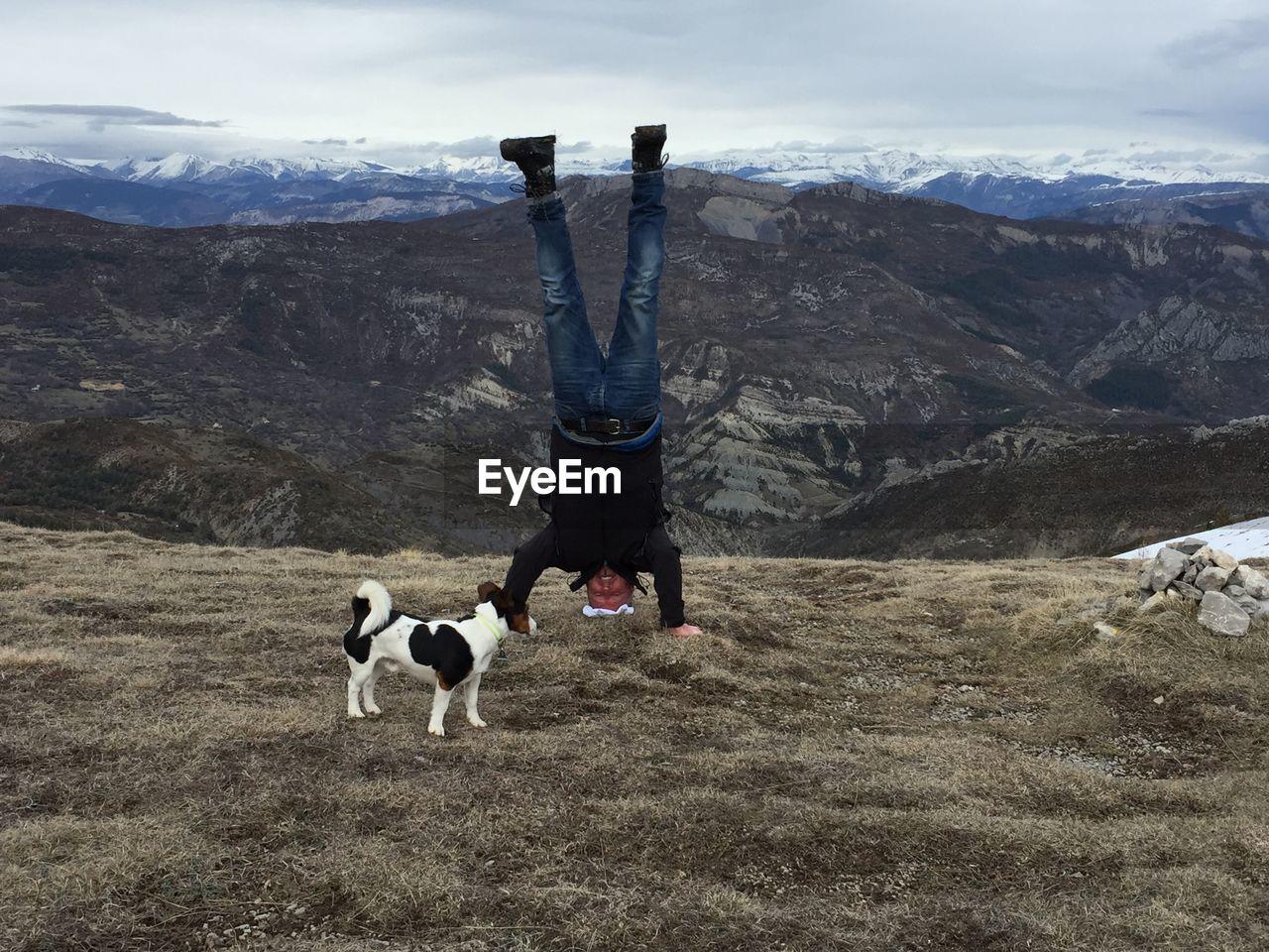 Full length of senior man doing headstand on mountain against cloudy sky