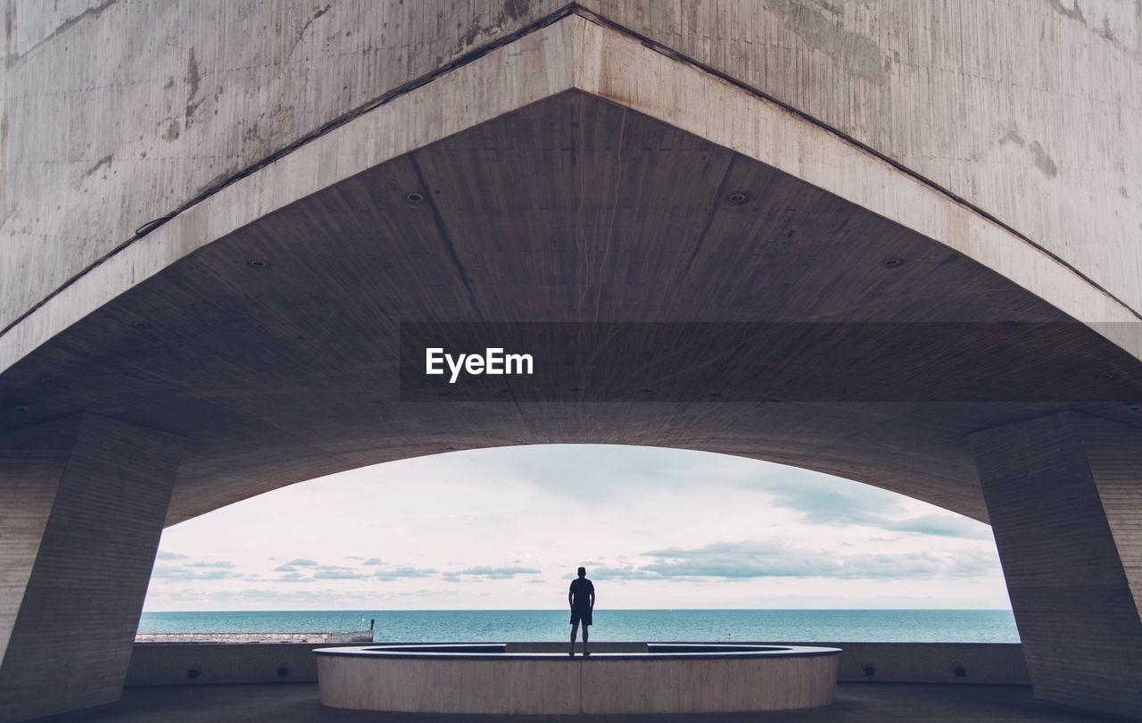 Rear View Of Man Standing Under Bridge By Sea