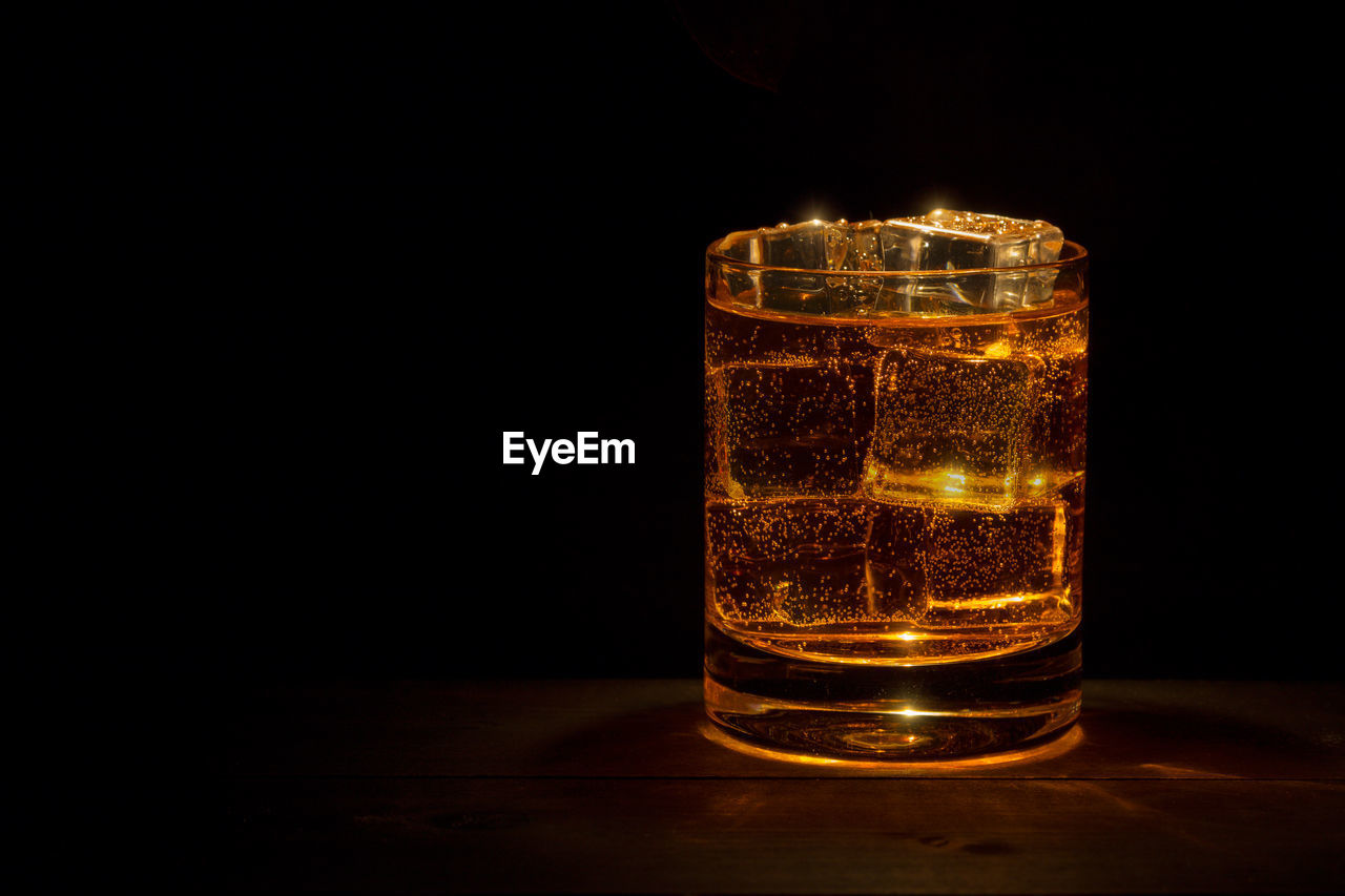 drinking glass, glass, indoors, refreshment, transparent, glass - material, household equipment, drink, copy space, table, food and drink, still life, no people, black background, studio shot, close-up, freshness, alcohol, cold temperature, whiskey