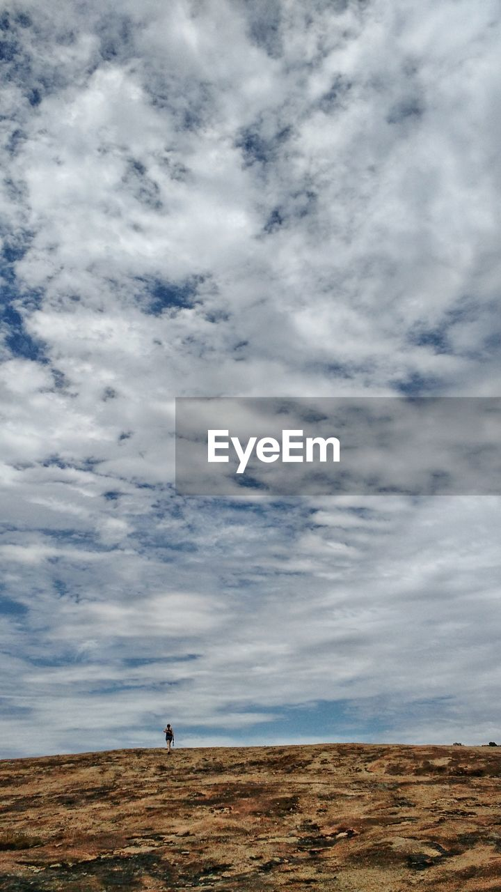 sky, cloud - sky, one person, landscape, nature, field, day, outdoors, beauty in nature, horizon over land, tranquility, standing, men, real people, arid climate, scenics, desert, one man only, people