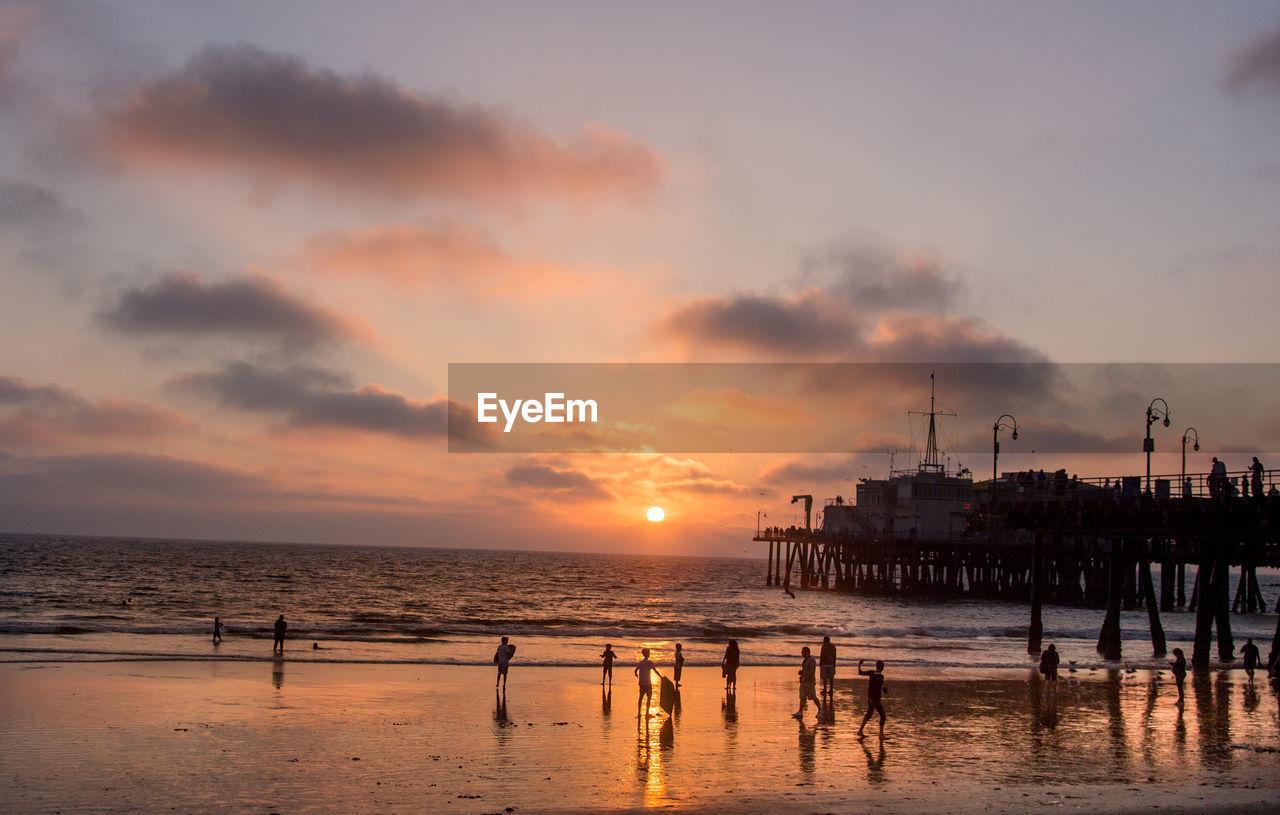 Crowd On Beach At Santa Monica Pier During Sunset