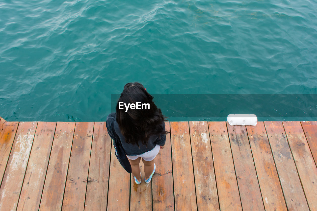 Rear View Of Woman Sitting On Pier Over Sea