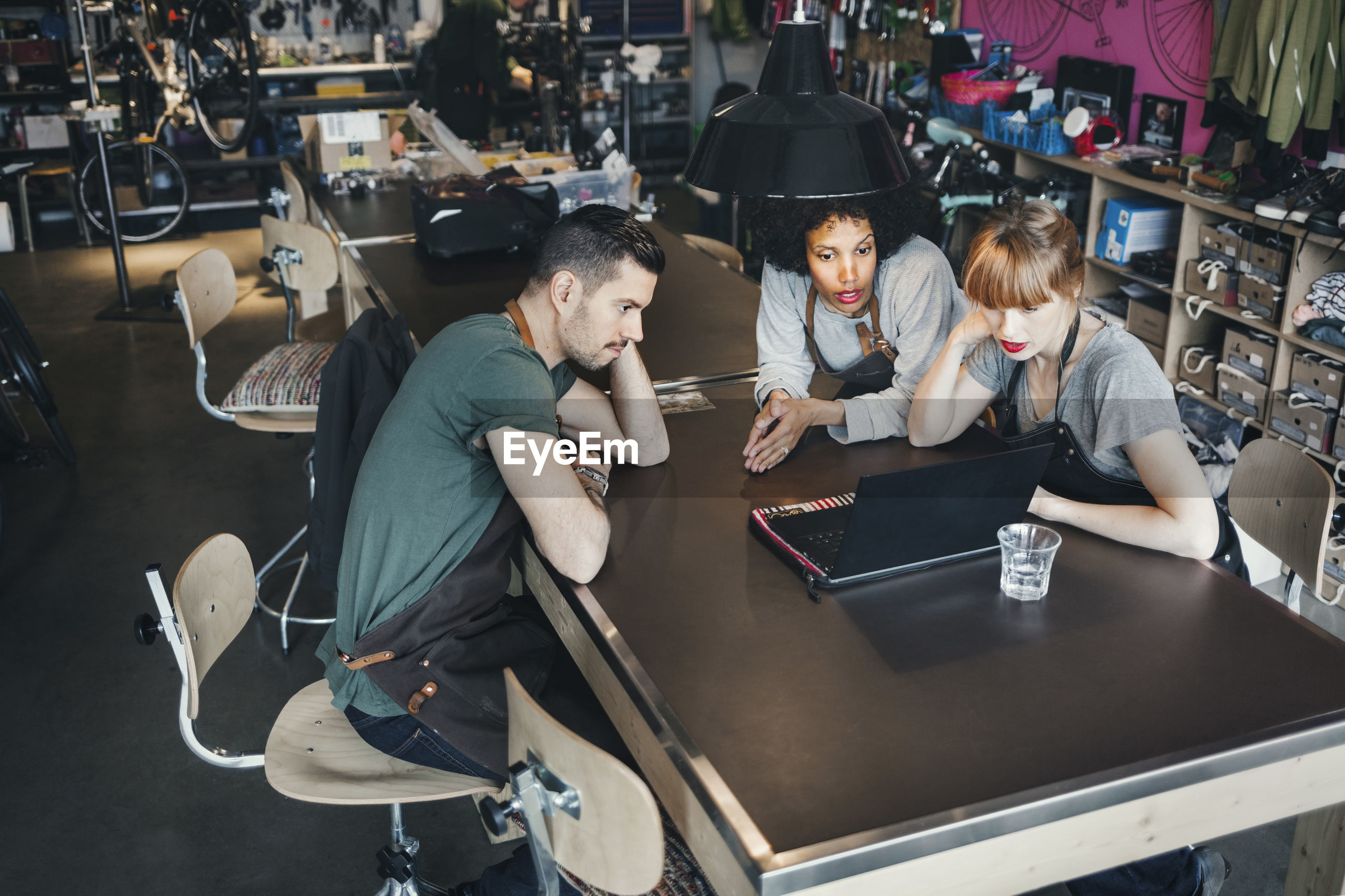 High angle view of mechanics using laptop at table in workshop