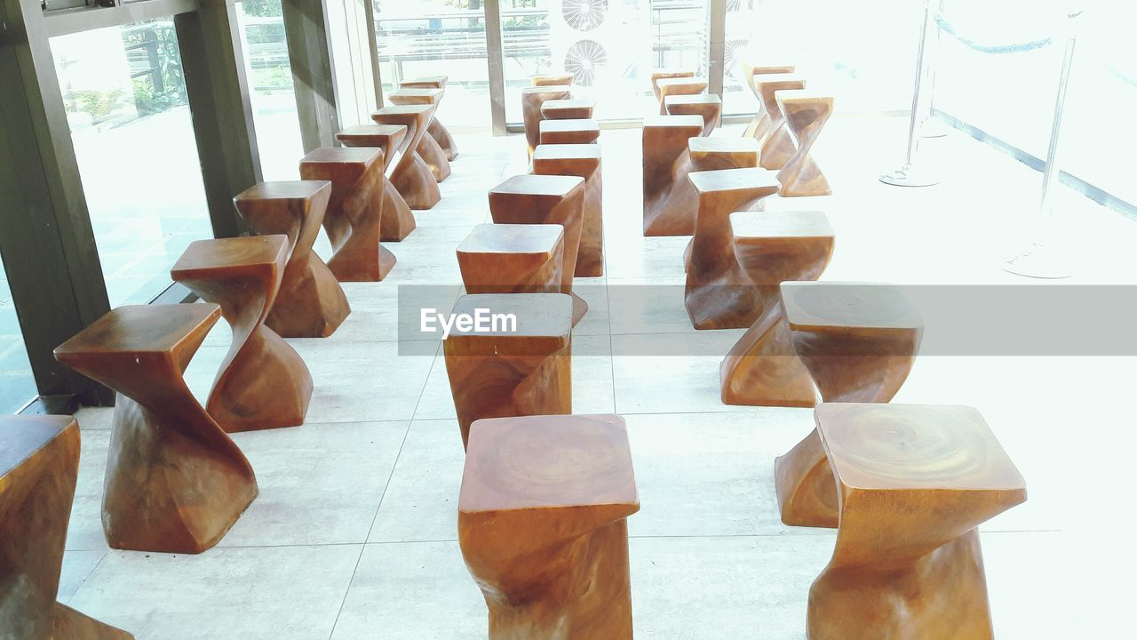 indoors, day, no people, table, in a row, still life, wood - material, flooring, window, brown, high angle view, glass, large group of objects, group, food and drink, side by side, focus on foreground, close-up, glass - material