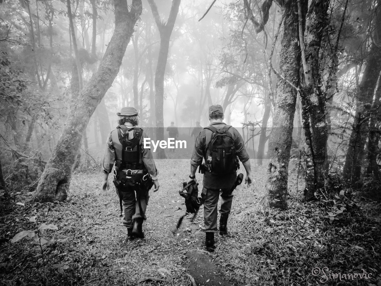 walking, backpack, forest, tree, rear view, teamwork, real people, adventure, two people, weapon, only men, helmet, full length, togetherness, courage, army soldier, hiking, adults only, uniform, nature, people, fog, military, challenge, men, day, army, firefighter, outdoors, young adult, friendship, adult, riot