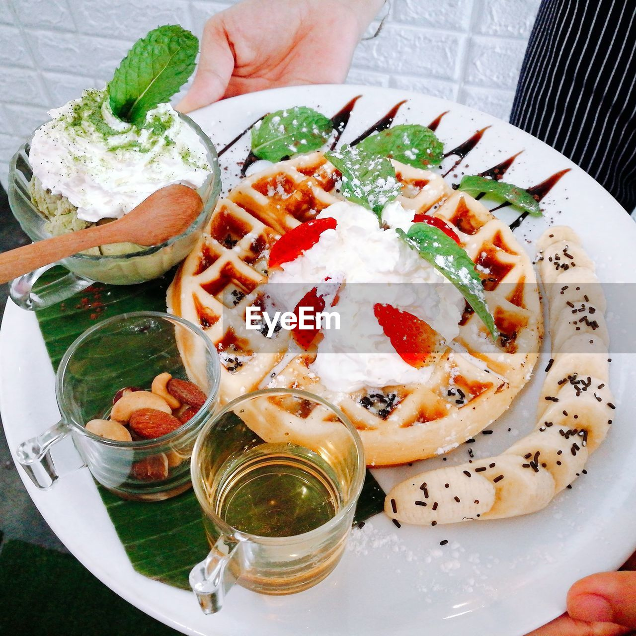 Cropped Hand Holding Food And Drink In Plate