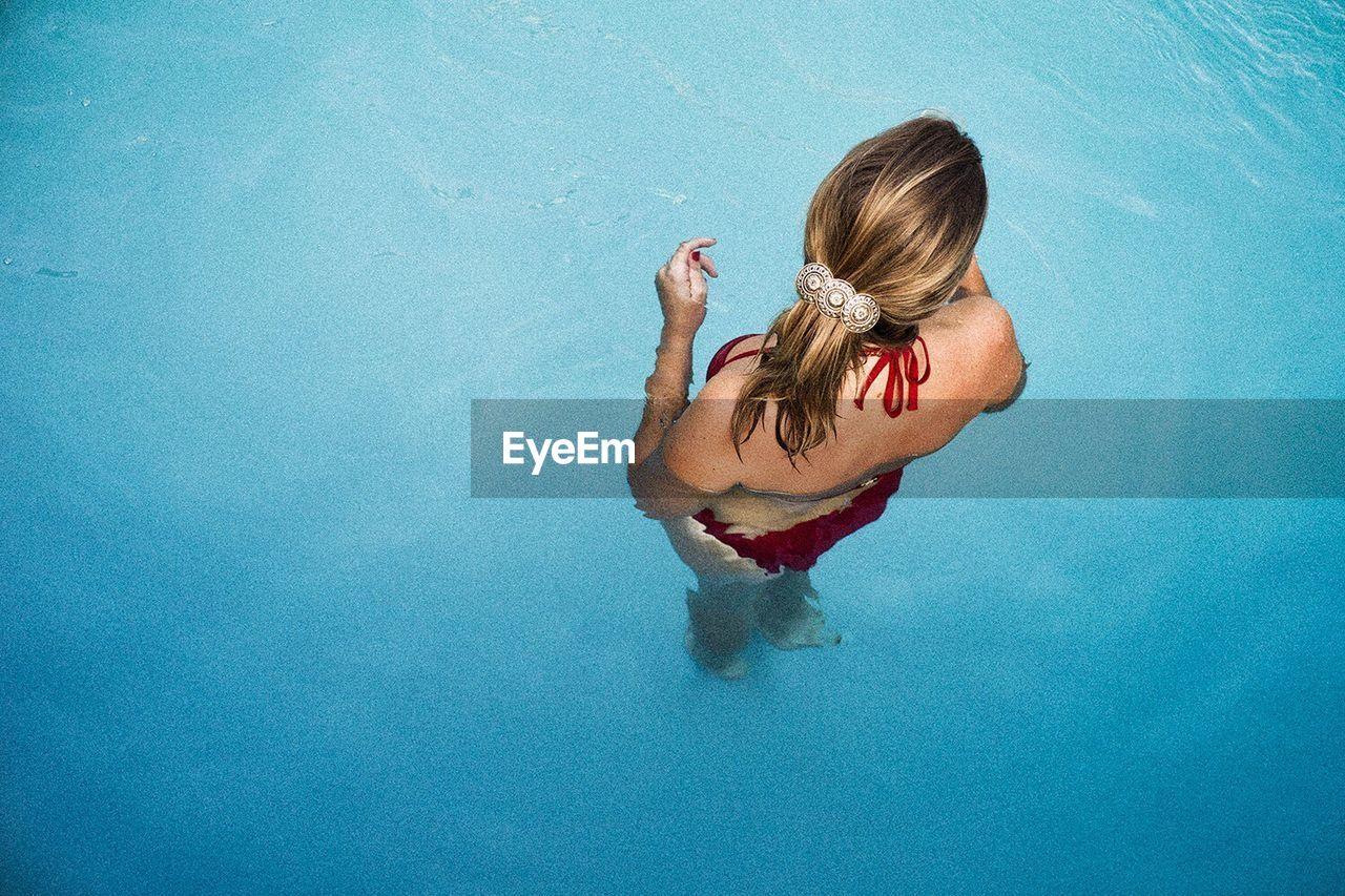 Rear View Of Woman Wearing Bikini In Swimming Pool