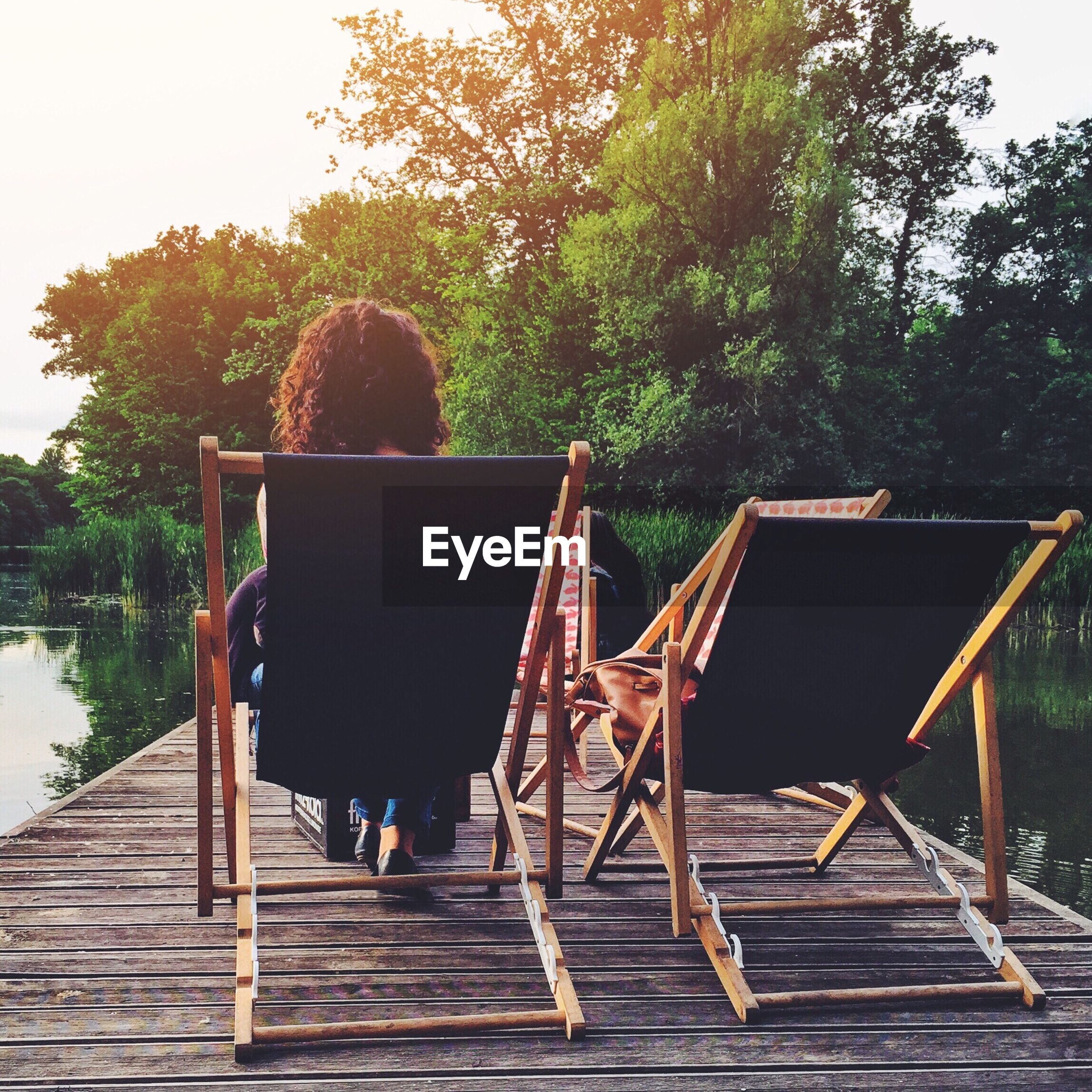 Rear view of woman relaxing on deck chair by river