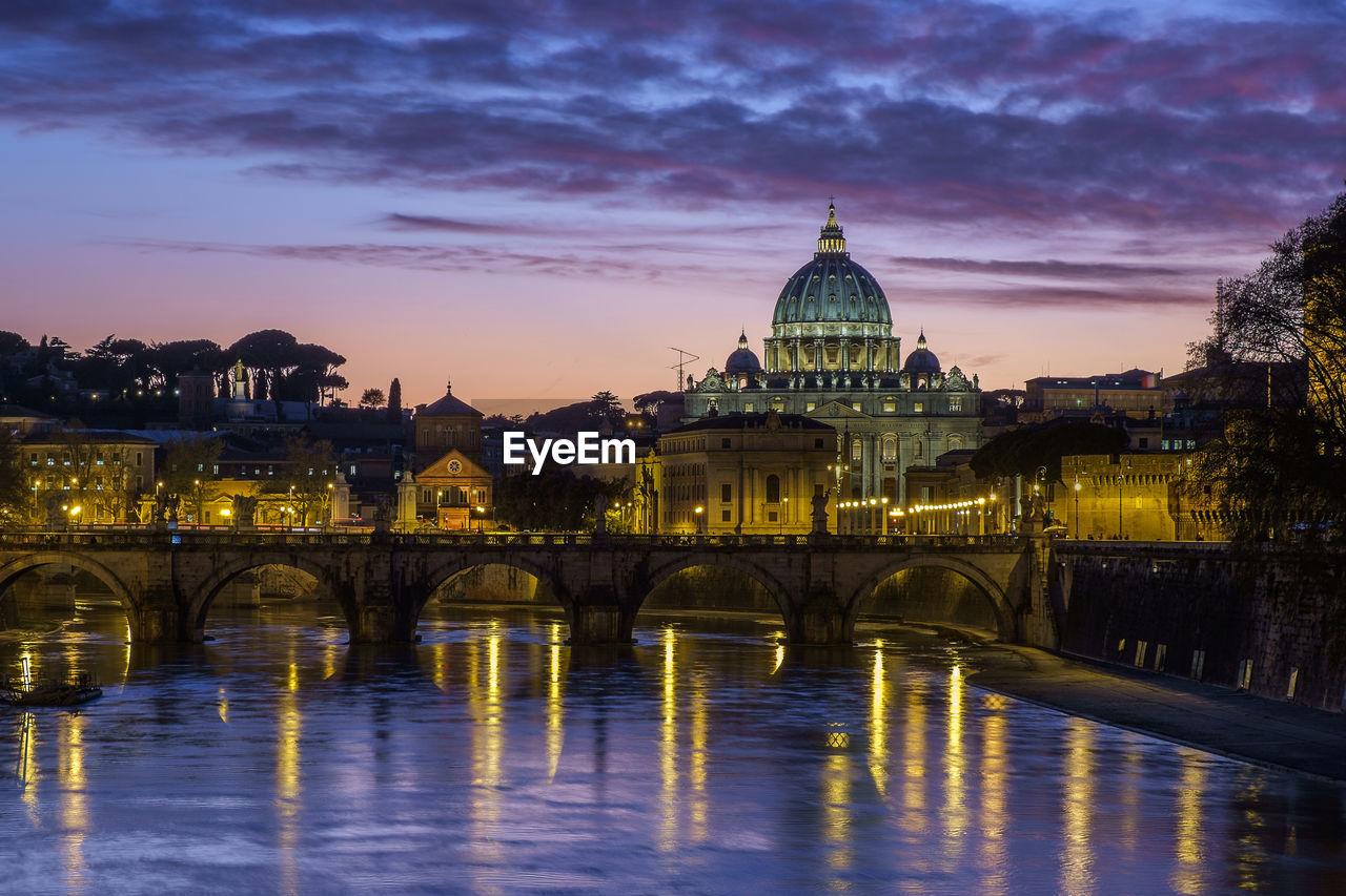 Illuminated Arch Bridge And St Peter Basilica Against Sky At Dusk