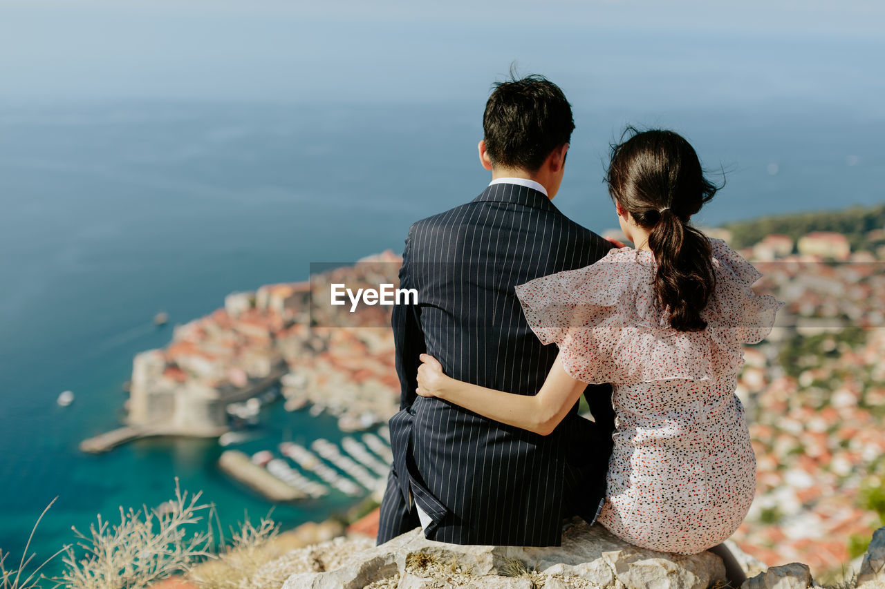 Rear View Of Married Couple Sitting On Rock Against Sea