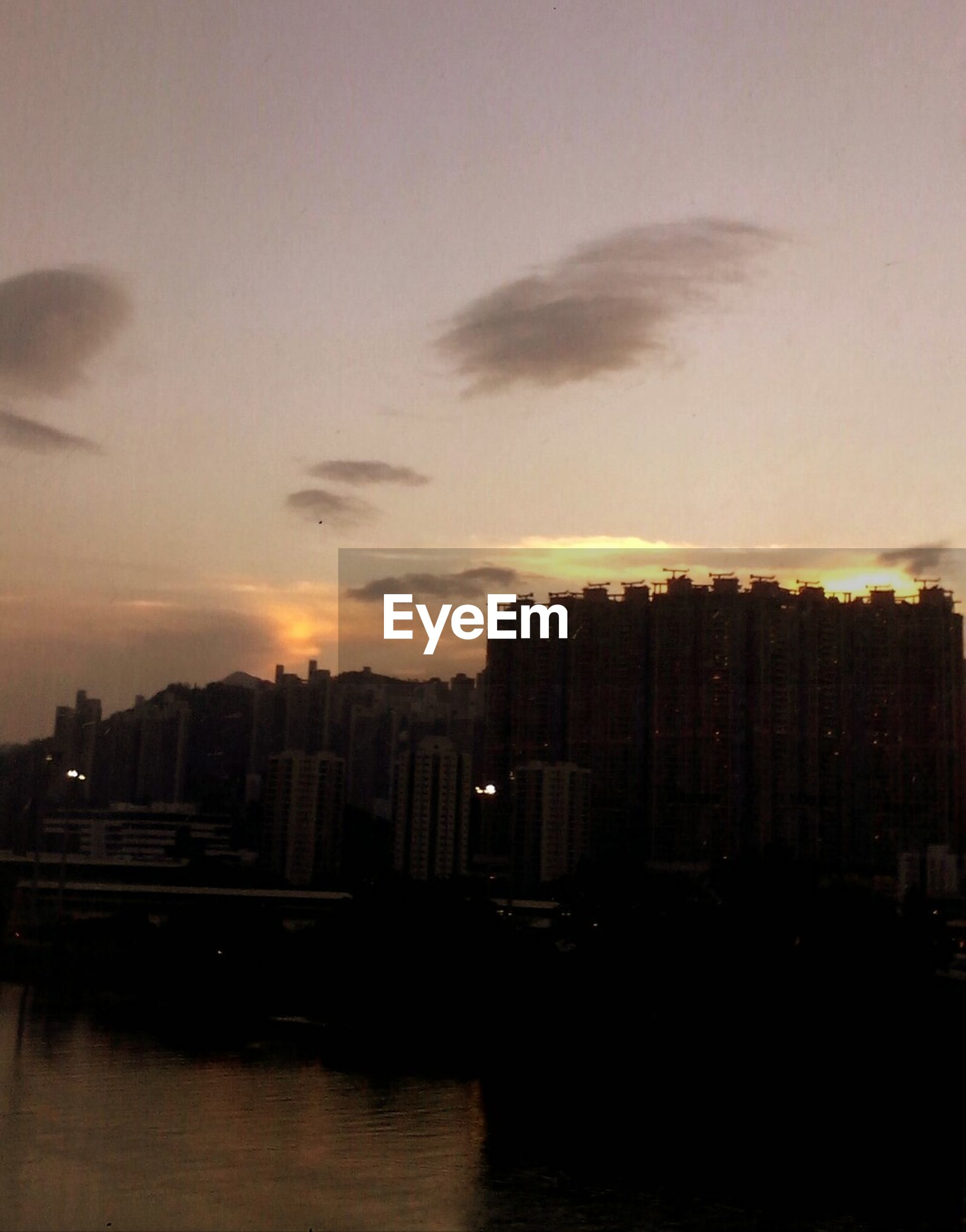 building exterior, architecture, sunset, built structure, city, sky, waterfront, cityscape, water, residential building, building, river, orange color, cloud - sky, residential structure, silhouette, residential district, reflection, skyscraper, city life