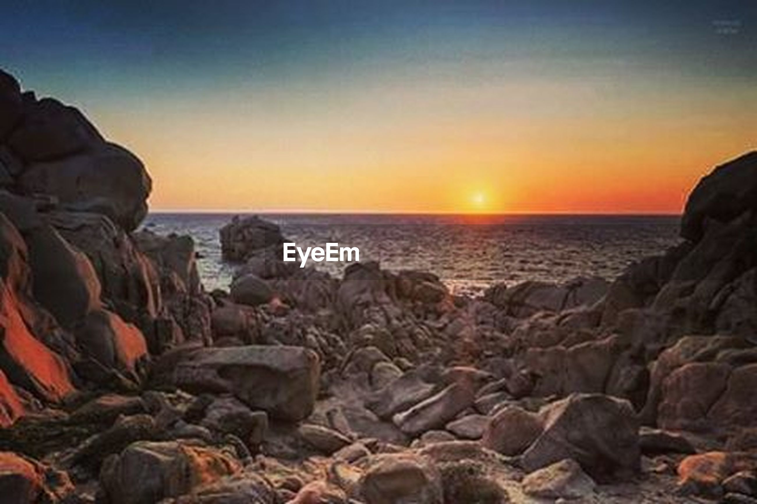 sea, sunset, horizon over water, water, scenics, rock - object, tranquil scene, tranquility, beauty in nature, rock formation, beach, nature, orange color, shore, sun, rock, idyllic, clear sky, sky, sunlight