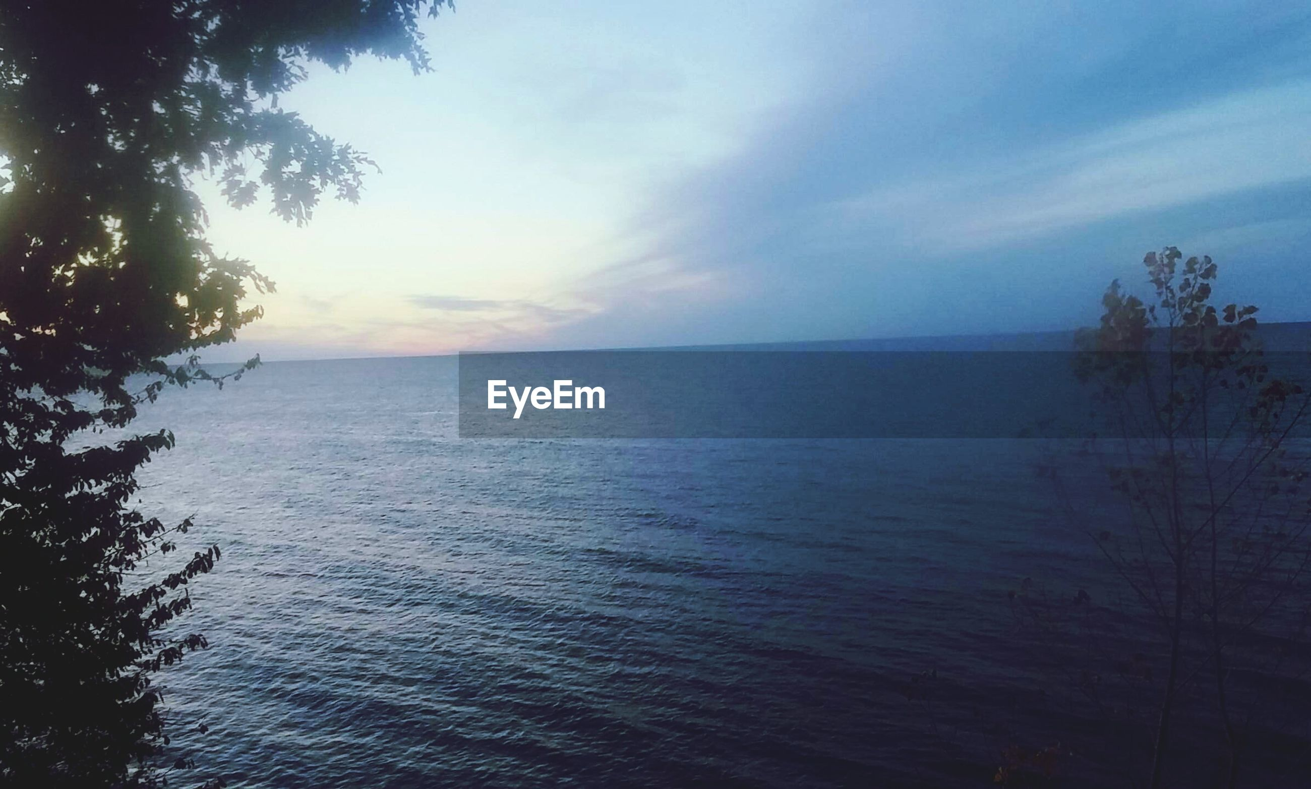 tranquil scene, horizon over water, sea, tranquility, scenics, water, beauty in nature, sky, nature, tree, idyllic, sunset, cloud - sky, cloud, seascape, outdoors, remote, rippled, no people, waterfront